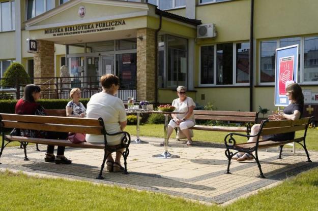Cztery kobiety siedzą na ławkach na świeżym powietrzu.