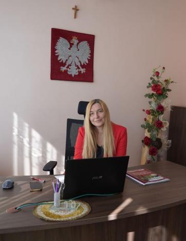 Na zdjęciu widoczna kobieta siedząca za biurkiem