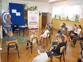 Pisarka w sali prowadzi spotkanie. Dzieci siedzą na krzesłach.