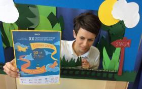 Bibliotekarka prezentuje plakat XX Ogólnopolskiego Tygodnia Czytania Dzieciom