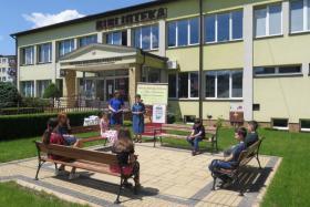 """Rozdanie nagród w Gminnym Konkursie Literackim """"Fraszka o bibliotekarzu"""" przed budynkiem biblioteki."""