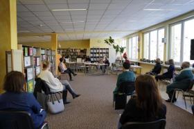 Wnętrze budynku osoby siedzą na krzesłach