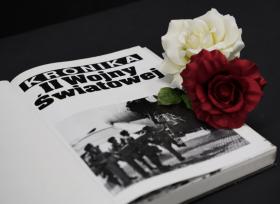 Na zdjęciu widoczna otwarta książka, obok dwie róże: biała i czerwona